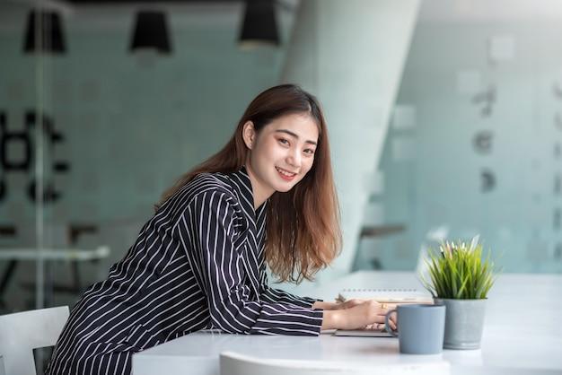 Młoda ładna bizneswoman azjatyckiego pracuje na laptopie siedząc przy stole w biurze