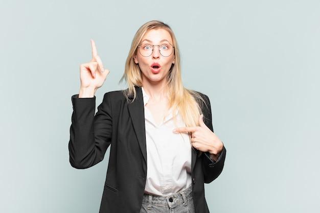 Młoda ładna bizneswoman czuje się dumna i zaskoczona, wskazując pewnie na siebie, czując się jak odnosząca sukcesy numer jeden