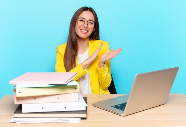 Młoda ładna bizneswoman czuje się szczęśliwa i odnosi sukcesy, uśmiechając się i klaszcząc w dłonie, gratulując z brawami