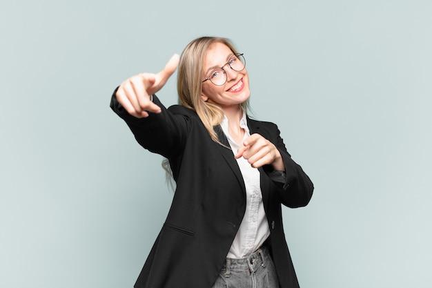 Młoda ładna bizneswoman czuje się szczęśliwa i pewna siebie, wskazując aparat obiema rękami i śmiejąc się, wybierając ciebie
