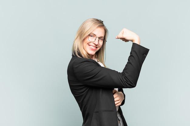 Młoda ładna bizneswoman czuje się szczęśliwa, usatysfakcjonowana i potężna, wygina się i ma umięśnione bicepsy, wygląda dobrze po siłowni