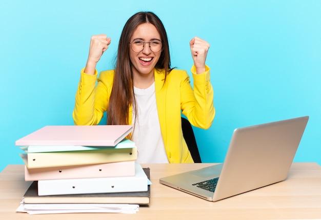 Młoda ładna bizneswoman czuje się szczęśliwa, zaskoczona i dumna, krzyczy i świętuje sukces z wielkim uśmiechem