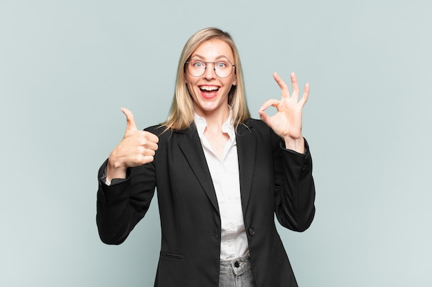 Młoda ładna bizneswoman czuje się szczęśliwa, zdumiona, usatysfakcjonowana i zaskoczona, pokazując gesty w porządku i kciuki w górę, uśmiechając się