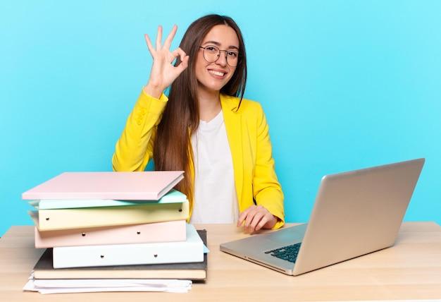 Młoda ładna bizneswoman czuje się szczęśliwa, zrelaksowana i usatysfakcjonowana, okazując aprobatę dobrym gestem, uśmiechając się