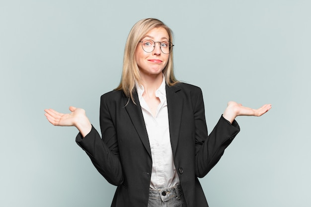 Młoda ładna bizneswoman czuje się zakłopotana i zdezorientowana, wątpi, waży lub wybiera różne opcje ze śmiesznym wyrazem twarzy