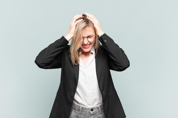 Młoda ładna bizneswoman czuje się zestresowana i sfrustrowana, podnosi ręce do głowy, czuje się zmęczona, nieszczęśliwa i z migreną