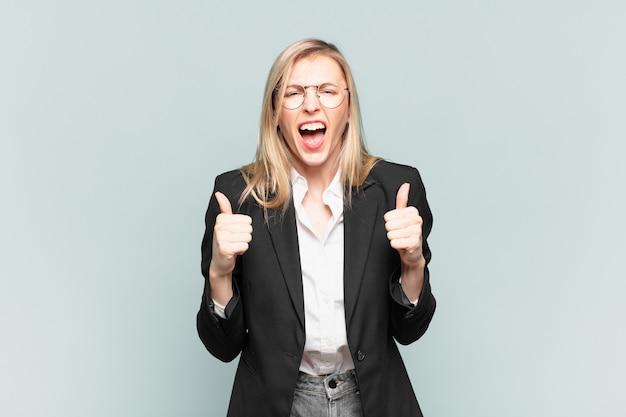 Młoda ładna bizneswoman krzyczy agresywnie ze zirytowanym, sfrustrowanym, gniewnym spojrzeniem i zaciśniętymi pięściami, czując się wściekły
