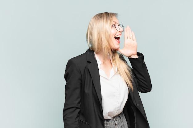 Młoda ładna bizneswoman krzyczy głośno i ze złością, aby skopiować miejsce z boku, z ręką przy ustach