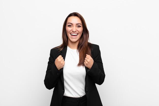 Młoda ładna bizneswoman krzyczy triumfalnie, śmiejąc się i czując się szczęśliwa i podekscytowana, świętując sukces przeciwko białej ścianie