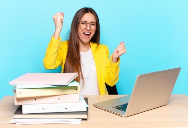 Młoda ładna bizneswoman krzyczy triumfalnie, wyglądając jak podekscytowany, szczęśliwy i zaskoczony zwycięzca, świętuje