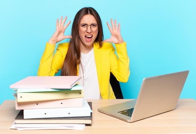 Młoda ładna bizneswoman krzyczy w panice lub gniewie, zszokowana, przerażona lub wściekła, z rękami obok głowy