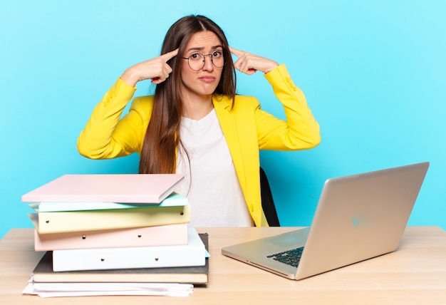Młoda ładna bizneswoman o poważnym i skoncentrowanym spojrzeniu, przeprowadzająca burzę mózgów i myśląca o trudnym problemie