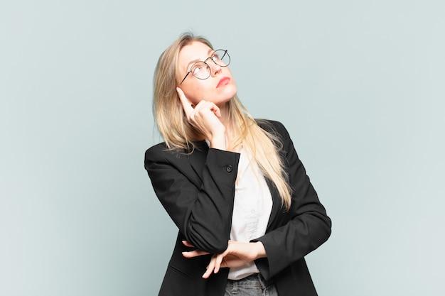 Młoda ładna bizneswoman o skoncentrowanym spojrzeniu, zastanawiająca się z wątpliwym wyrazem twarzy, patrząca w górę i w bok