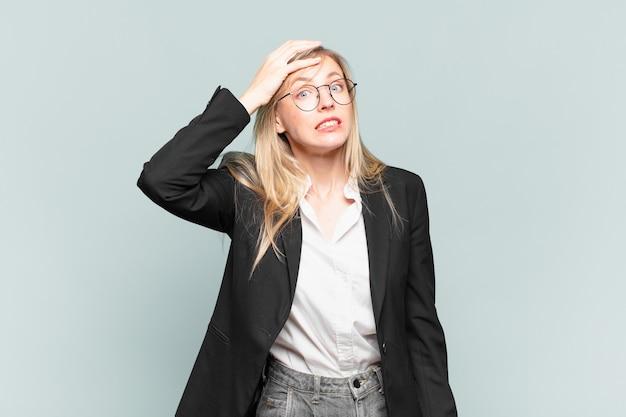 Młoda ładna bizneswoman panikuje nad zapomnianym terminem, czuje się zestresowana, musi zatuszować bałagan lub błąd