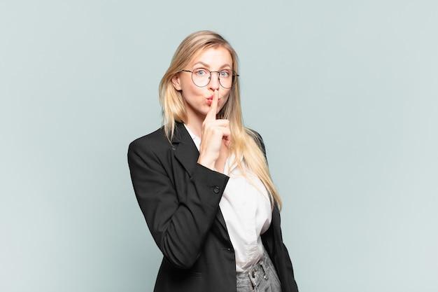 Młoda ładna bizneswoman prosząca o ciszę i spokój, gestykulująca palcem przed ustami, mówiąca ćśśśś lub dochować tajemnicy