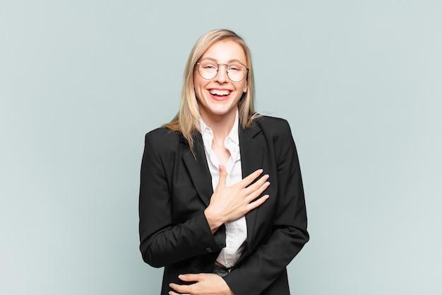 Młoda ładna bizneswoman śmiejąca się głośno z jakiegoś przezabawnego żartu, szczęśliwa i wesoła, dobrze się bawi