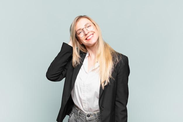 Młoda ładna bizneswoman śmiejąca się radośnie i pewnie ze swobodnym, radosnym, przyjaznym uśmiechem