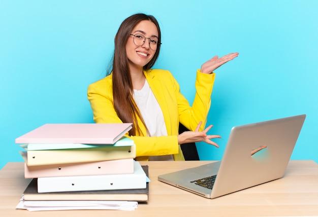 Młoda ładna bizneswoman uśmiecha się dumnie i pewnie, czuje się szczęśliwa i usatysfakcjonowana i pokazuje koncepcję na przestrzeni kopii
