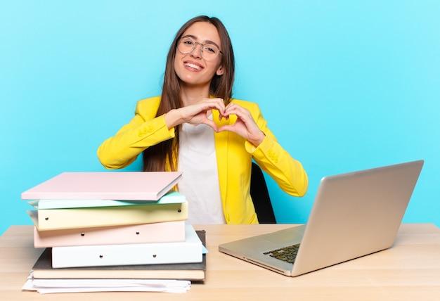 Młoda ładna bizneswoman uśmiecha się i czuje się szczęśliwa, słodka, romantyczna i zakochana, tworząc kształt serca obiema rękami