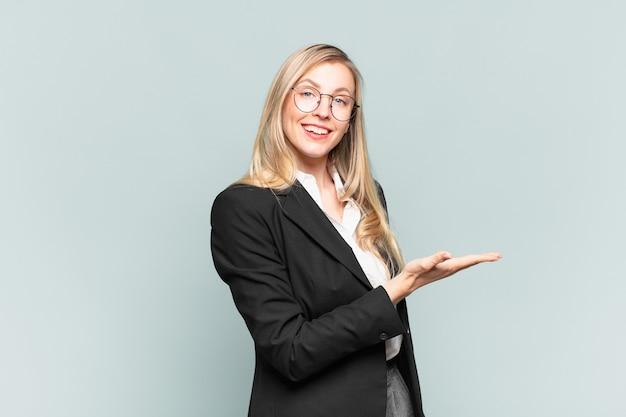 Młoda ładna bizneswoman uśmiecha się radośnie, czuje się szczęśliwa i pokazuje koncepcję w przestrzeni kopii z dłonią