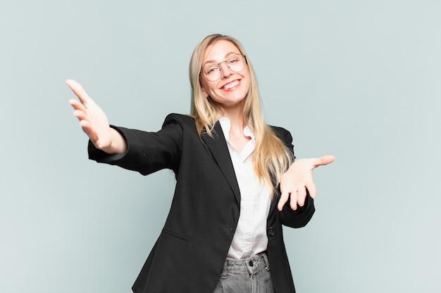Młoda ładna bizneswoman uśmiecha się radośnie, dając ciepły, przyjazny, pełen miłości uścisk powitalny, czując się szczęśliwa i urocza