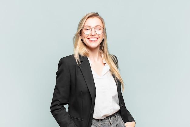 Młoda ładna bizneswoman uśmiecha się radośnie i od niechcenia z pozytywnym, szczęśliwym, pewnym siebie i zrelaksowanym wyrazem twarzy