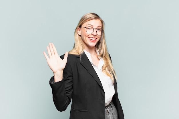 Młoda ładna bizneswoman uśmiecha się radośnie i radośnie, machając ręką, witając cię i witając lub żegnając się