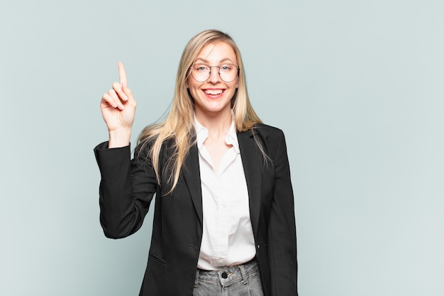 Młoda ładna bizneswoman uśmiecha się radośnie i radośnie, wskazując jedną ręką w górę, aby skopiować przestrzeń