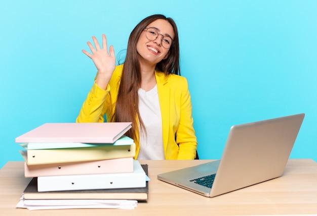 Młoda ładna bizneswoman uśmiecha się radośnie i wesoło, macha ręką, wita i wita lub żegna się