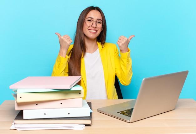 Młoda ładna bizneswoman uśmiecha się radośnie i wygląda na szczęśliwą, czuje się beztrosko i pozytywnie z dwoma kciukami do góry