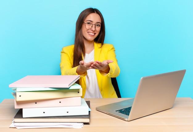 Młoda ładna bizneswoman uśmiecha się radośnie z przyjaznym, pewnym siebie, pozytywnym spojrzeniem, oferuje i pokazuje przedmiot lub koncepcję