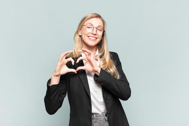 Młoda ładna bizneswoman uśmiechnięta i czująca się szczęśliwa, urocza, romantyczna i zakochana, tworząca kształt serca obiema rękami