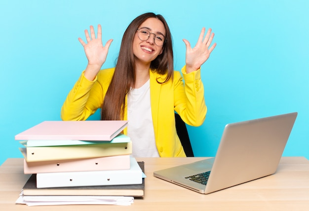 Młoda ładna bizneswoman uśmiechnięta i przyjazna, pokazując numer dziesięć lub dziesiątą ręką do przodu