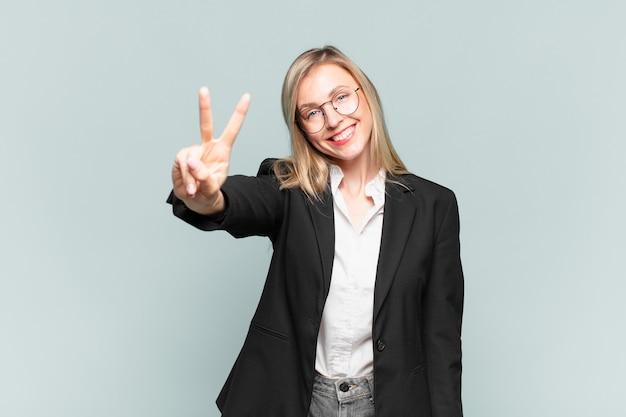 Młoda ładna bizneswoman uśmiechnięta i wyglądająca na szczęśliwą, beztroską i pozytywną, gestykulującą zwycięstwo lub pokój jedną ręką