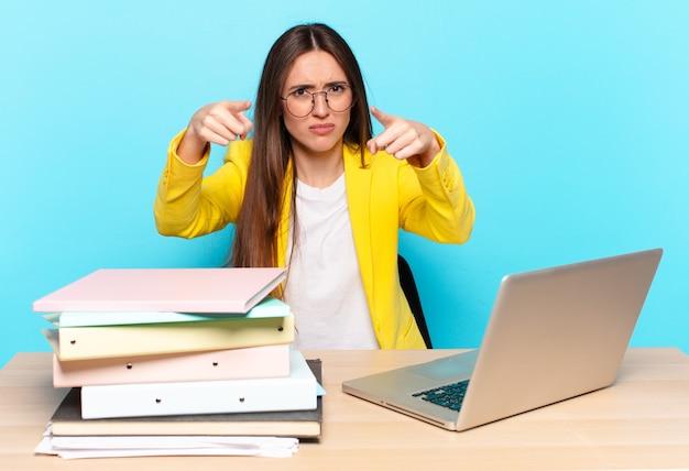 Młoda ładna bizneswoman, wskazująca do przodu z przodu palcami i gniewnym wyrazem twarzy, mówiąca, abyś wypełnił swój obowiązek