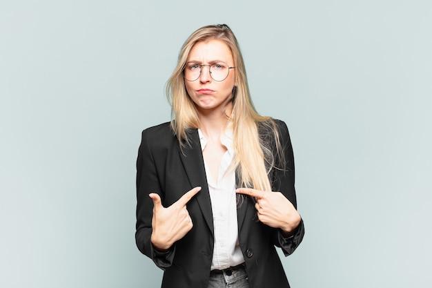 Młoda ładna bizneswoman wskazująca na siebie z zakłopotanym i zagadkowym spojrzeniem, zszokowana i zaskoczona wyborem