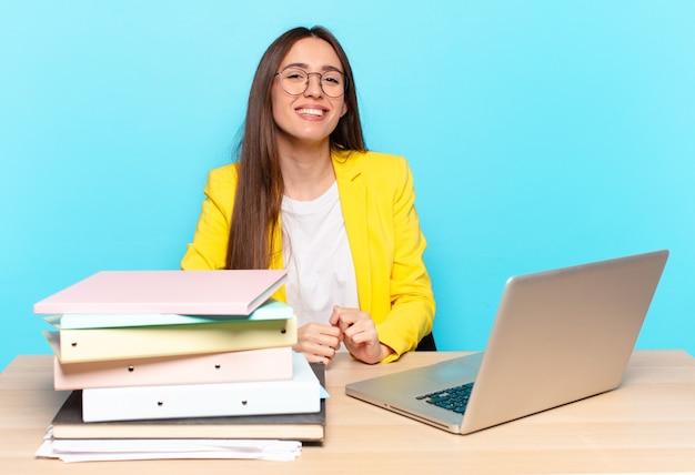 Młoda ładna bizneswoman wygląda na szczęśliwą i głupawą z szerokim, zabawnym, szalonym uśmiechem i szeroko otwartymi oczami