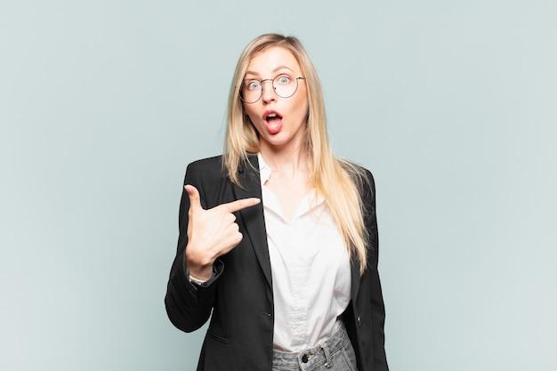 Młoda ładna bizneswoman wygląda na zszokowaną i zaskoczoną z szeroko otwartymi ustami, wskazując na siebie