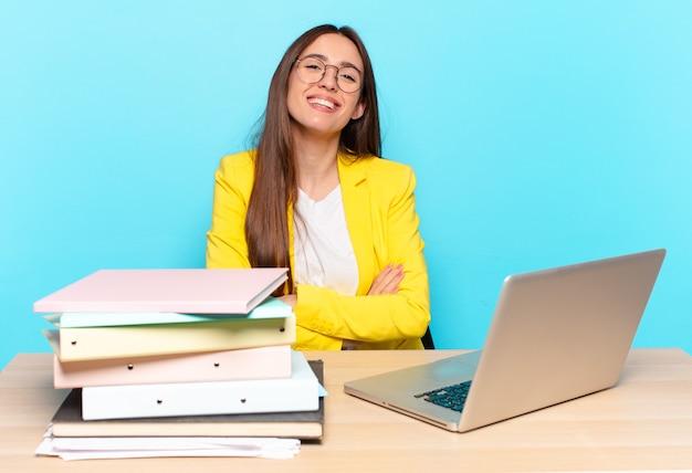 Młoda ładna bizneswoman wyglądająca jak szczęśliwa, dumna i zadowolona osoba, która osiągnęła sukces, uśmiechnięta z założonymi rękami