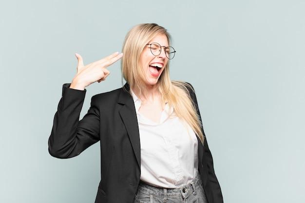 Młoda ładna bizneswoman wyglądająca na niezadowoloną i zestresowaną, gest samobójczy, który robi znak pistoletu ręką, wskazując na głowę