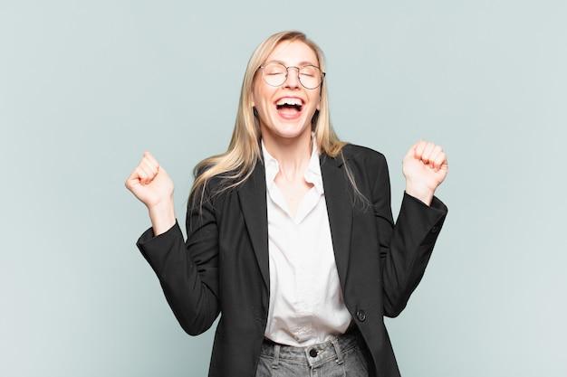 Młoda ładna bizneswoman wyglądająca na niezwykle szczęśliwą i zaskoczoną, świętującą sukces, krzyczącą i skaczącą