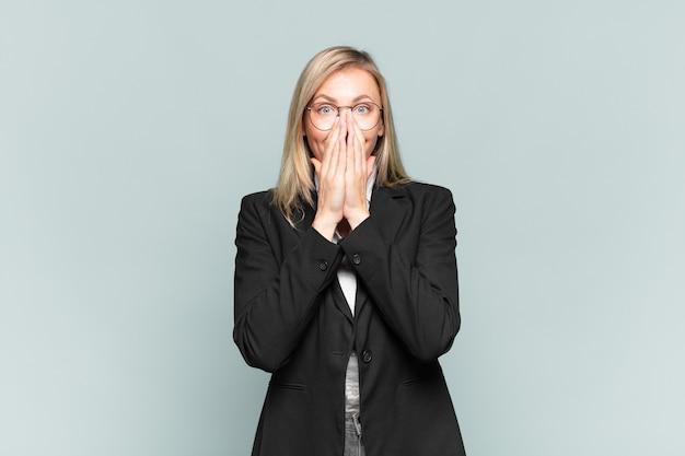 Młoda ładna bizneswoman wyglądająca na szczęśliwą, wesołą, szczęśliwą i zdziwioną zakrywającą usta obiema rękami