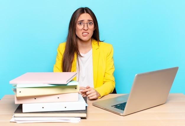Młoda ładna bizneswoman wyglądająca na zakłopotaną i zdezorientowaną, przygryza wargę nerwowym gestem, nie znając odpowiedzi na problem