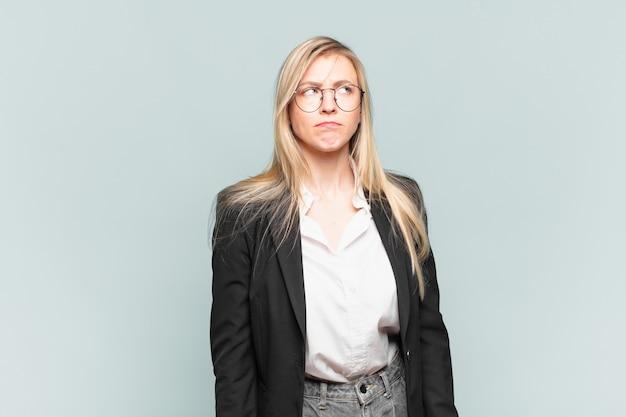 Młoda ładna bizneswoman wyglądająca na zdziwioną i zdezorientowaną, zastanawiającą się lub próbującą rozwiązać problem lub myślącą