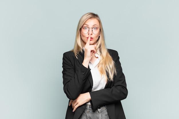 Młoda ładna bizneswoman wyglądająca poważnie i skrzyżowana z palcem przyciśniętym do ust, domagająca się ciszy lub spokoju, dochowania tajemnicy