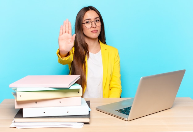 Młoda ładna bizneswoman wyglądająca poważnie, surowo, niezadowolona i zła, pokazując otwartą dłoń, robiąc gest zatrzymania