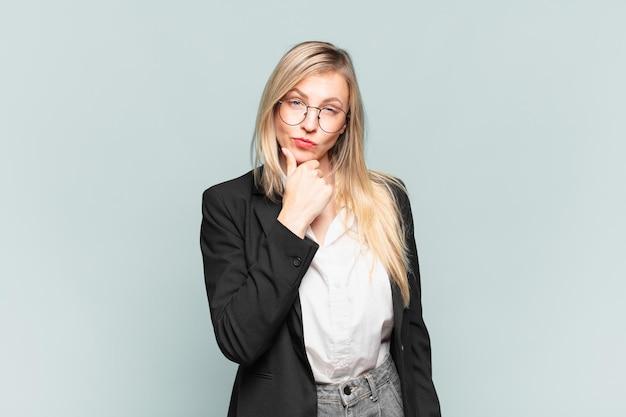 Młoda ładna bizneswoman wyglądająca poważnie, zdezorientowana, niepewna i zamyślona, wątpiąca w opcje lub wybory