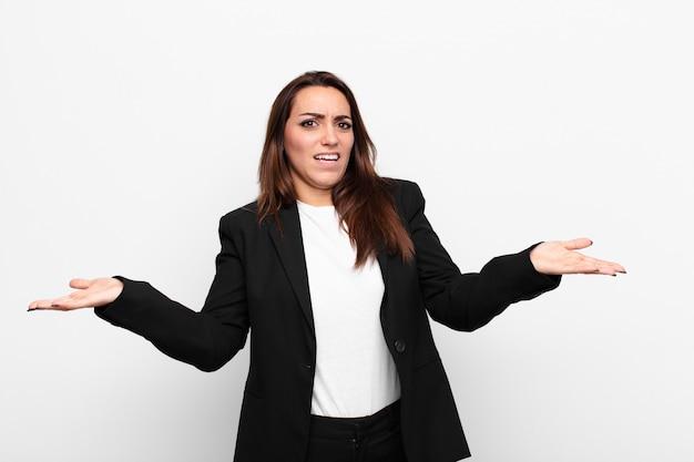 Młoda ładna bizneswoman wzrusza ramionami z głupim, szalonym, zdezorientowanym, zdziwionym wyrazem twarzy, czując się zirytowana i nieświadoma białej ściany