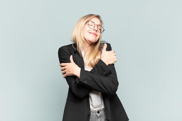 Młoda ładna bizneswoman zakochana, uśmiechnięta, przytulająca się i przytulająca siebie, pozostająca singlem, samolubna i egocentryczna