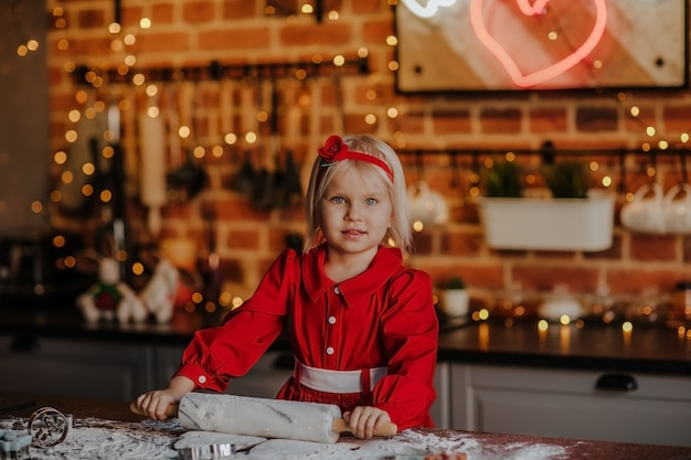 Młoda ładna blond dziewczyna w czerwonej sukni zimowej gotowania w kuchni z tłem bożego narodzenia
